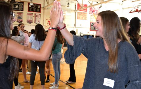 Juniors Ellie Decker and Alexis Lombardo laugh while training at a Peer Leadership Program event on June 6 at school. Nearly 70 rising seniors are getting ready to lead groups of freshmen starting in August.