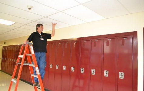 Custodian Ivan Barbalho fixing the ceiling tiles.