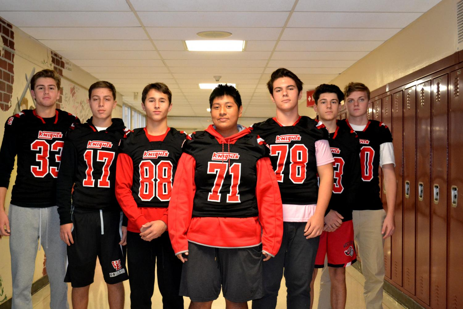 Football players show off their new uniforms.