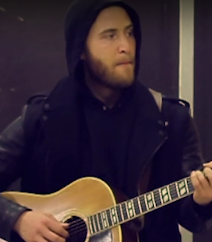 Mike Posner playing his guitar.