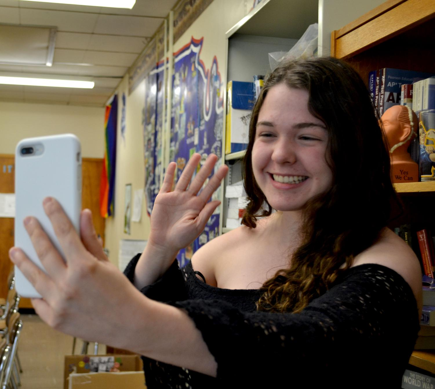 Evie Klein waves to her followers as she livestreams to teach AP U.S. History.