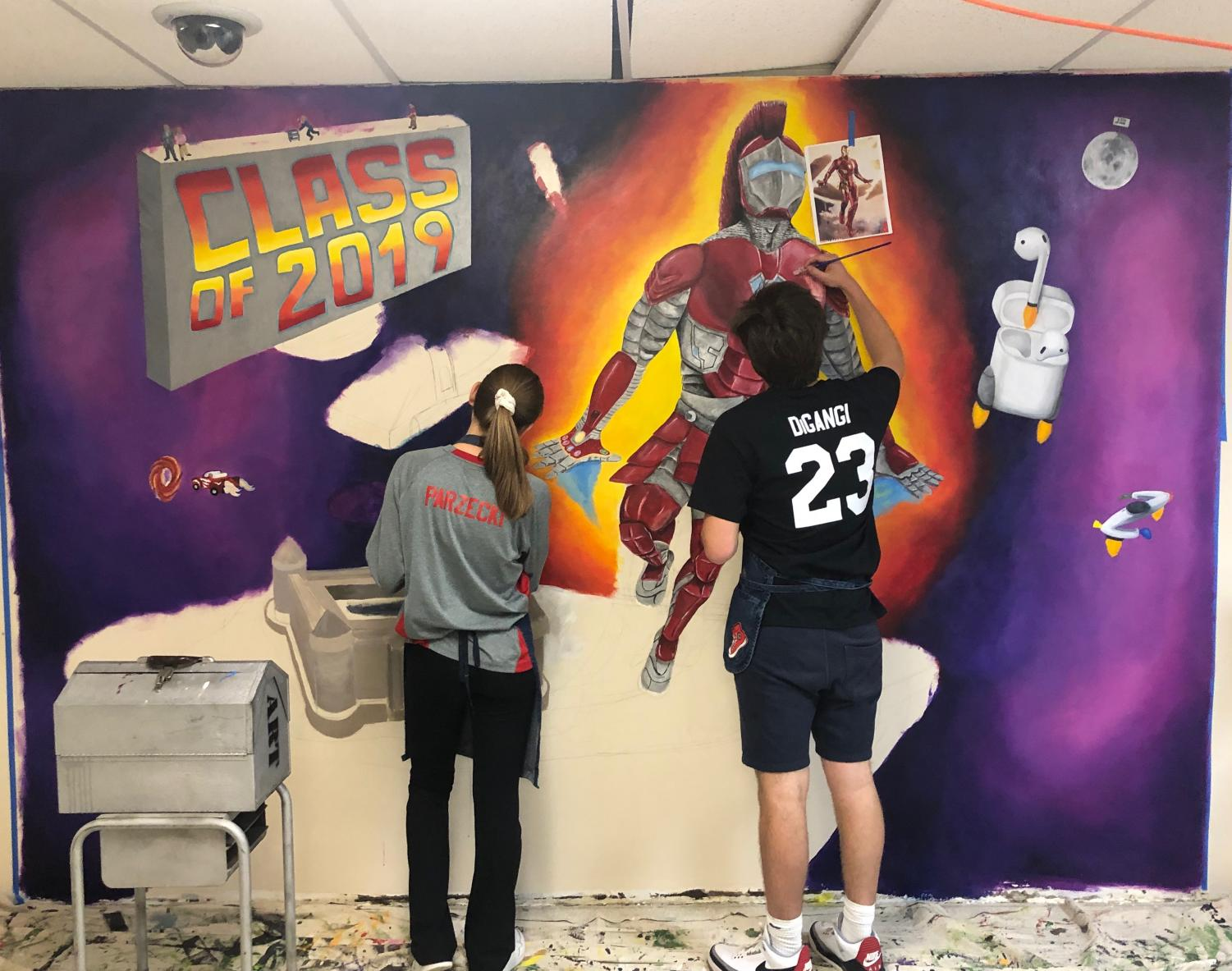 Seniors Mark DiGangi and Julia Parzecki continue painting the class of 2019 mural.