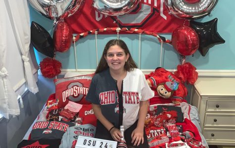 Senior Julia Rubenstein sits on her college themed bed decorated by her friends.