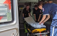 Senior Avery Shaw working with fellow EMTs to set up ambulance.