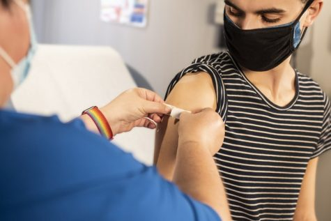 A healthcare worker is placing a bandage on a woman after receiving her vaccine, taken February 2, 2021.